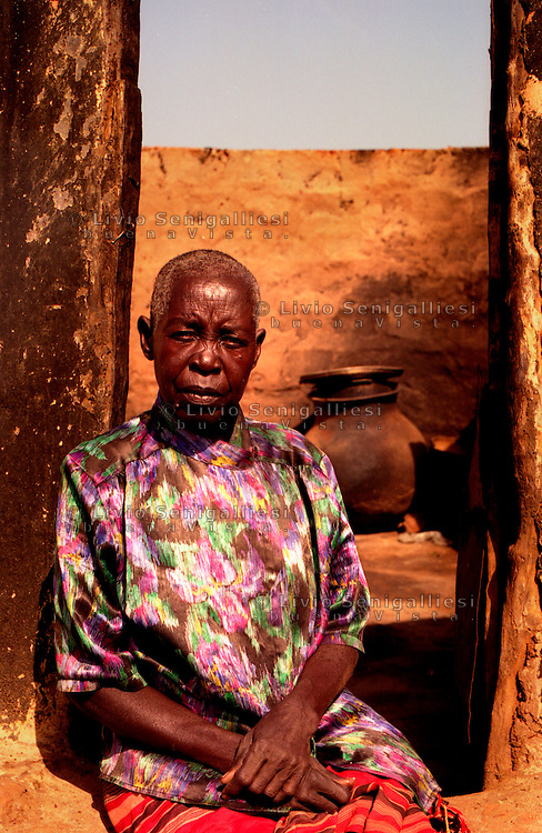 PAGAK / NORD UGANDA.UN'ANZIANA DONNA ACHOLI SIEDE SULLA SOGLIA DELLA SUA CAPANNA BRUCIATA DAI RIBELLI DURANTE UNA RECENTE INCURSIONE..FOTO LIVIO SENIGALLIESI..PAGAK / NORTH UGANDA.OLD ACHOLI WOMAN IN FRONT OF HER HUT DESTROIED BY LRA REBELS..PHOTO LIVIO SENIGALLIESI