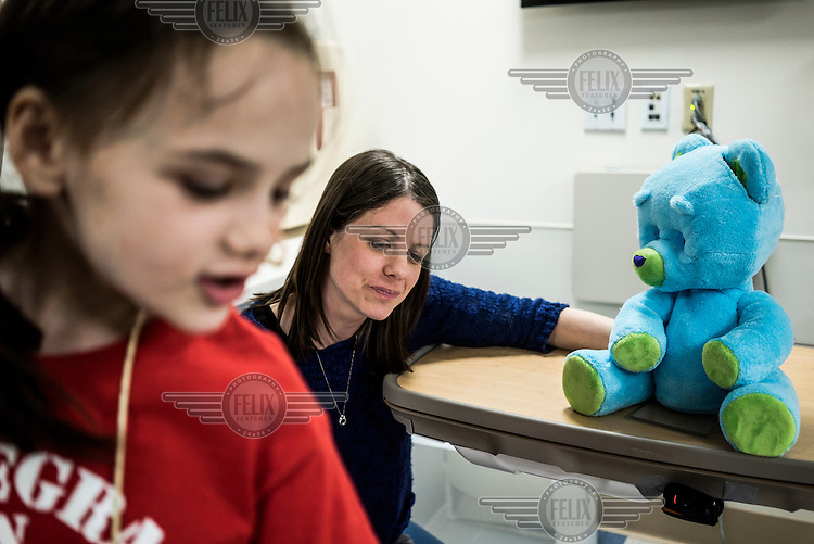 8-year old Beatrice Lipp plays 'I Spy' next to a 'Huggable' with the robotic teddy bear in an hospital room at Boston Children's Hospital while a hospital child-life specialist looks on. Beatrice has been in and out of Hospitals for the last 5 years. Now at Boston Children's Hospital, she is part of a social robotic experiment between Boston's Children Hospital and the Massachusetts Institute of Technology (MIT). The goal of the experiment is to determine whether a so called 'Huggable' teddy bear, a social robotic stereotype, can have therapeutic value for children who have to endure long hospital stays. The bear's talking and movements are remotely controlled by Hospital Staff from outside of the room.