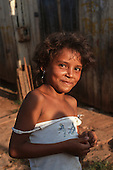 Xapuri, Acre State, Brazil. Smiling girl rubber tapper outside her wooden house.