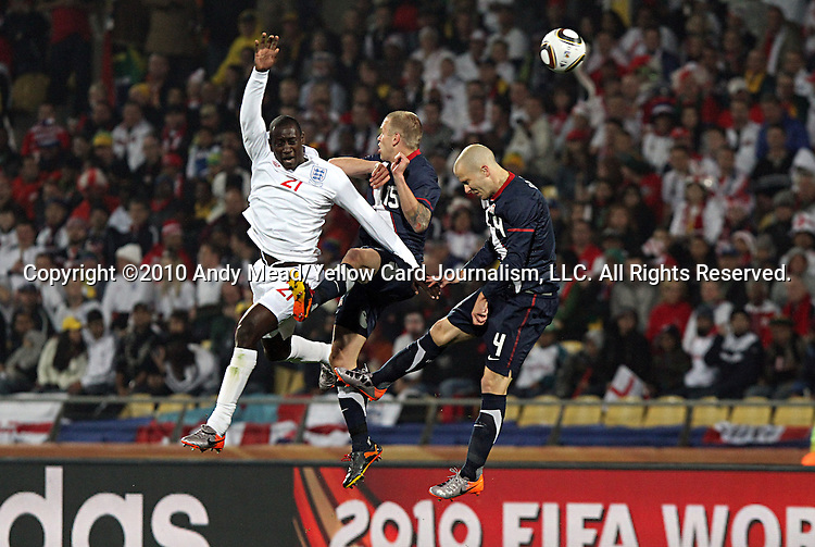 12 JUN 2010:  Emile Heskey (ENG)(21), Jay DeMerit (USA)(15), and Michael Bradley (USA) compete for a head ball.  The England National Team and the United States National Team were tied 1-1 after the first half at Royal Bafokeng Stadium in Rustenburg, South Africa in a 2010 FIFA World Cup Group C match.
