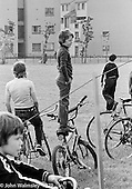 "Balancing on his ""Chopper"" bike to get a better view, Education Centre, Festival & Gala Day, Wester Hailes, Scotland, 1979.  John Walmsley was Photographer in Residence at the Education Centre for three weeks in 1979.  The Education Centre was, at the time, Scotland's largest purpose built community High School open all day every day for all ages from primary to adults.  The town of Wester Hailes, a few miles to the south west of Edinburgh, was built in the early 1970s mostly of blocks of flats and high rises."