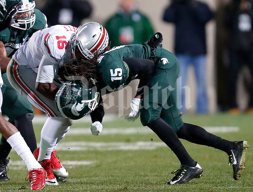 Michigan State Spartans cornerback Trae Waynes (15) loses his helmet as he collides with Ohio State Buckeyes quarterback J.T. Barrett (16) in the first quarter of the college football game between the Ohio State Buckeyes and the Michigan State Spartans at Spartan Stadium in East Lansing, Saturday night, November 8, 2014. (The Columbus Dispatch / Eamon Queeney)
