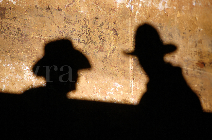 Two cowboys in hats form shadows against an adobe wall.