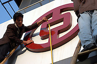 Workers putting up the logo of the Bank of China on the sign of a branch in Xian, China..