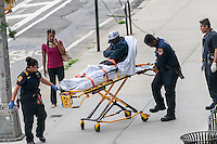 FDNY Emergency Service Technicians assist a homeless individual sleeping on the sidewalk in the Chelsea neighborhood of New York on Wednesday, July 3, 2016. (© Richard B. Levine)