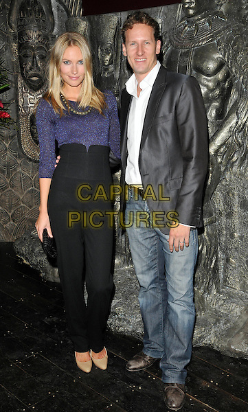 ZOE HOBBS & BRENDAN COLE .Launch Party for 'Shaka Zulu' Private Members Club at Stables market, Camden,  London, England, UK,.August 4th 2010.full length couple blue top black trousers  high waisted blazer jacket jeans white shirt clutch bag beige nude shoes .CAP/CAN.©Can Nguyen/Capital Pictures.