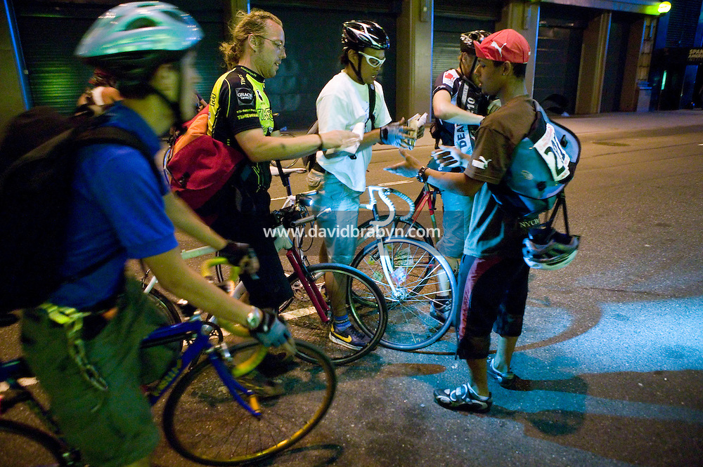 3 July 2005 - New York City, NY, USA - Riders get their manifests stamped by &quot;Junjun&quot; (R) at an alleycat checkpoint on 43rd street in New York City, USA, July 3rd 2005. Alleycats are urban cycle races held informally - without notification of the authorities - on open roads and in real traffic, to simulate the messenger's working conditions. Photo Credit: David Brabyn<br />