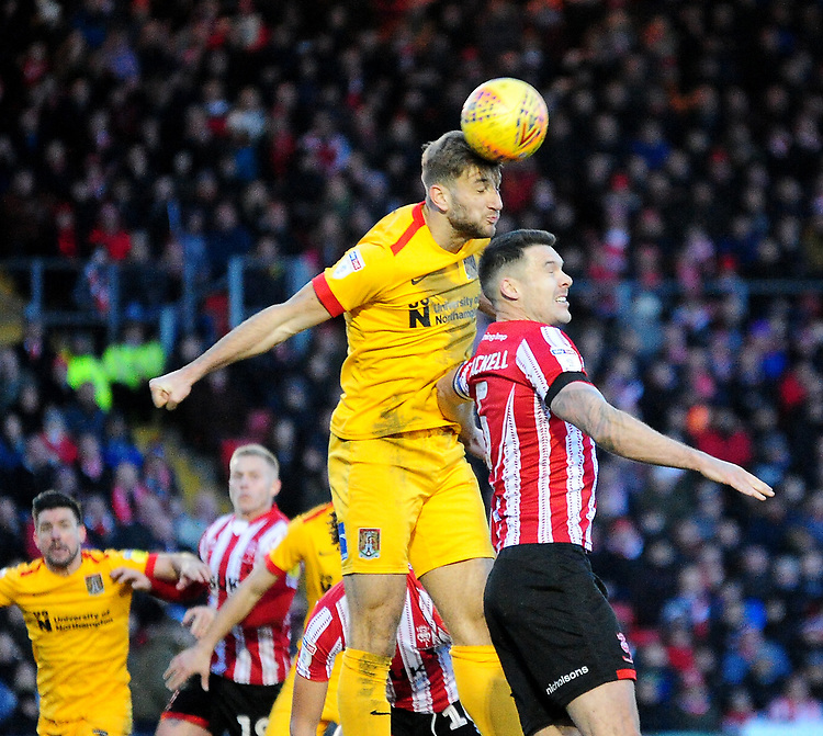 Lincoln City's Jason Shackell vies for possession with  Northampton Town's Ash Taylor<br /> <br /> Photographer Andrew Vaughan/CameraSport<br /> <br /> The EFL Sky Bet League Two - Lincoln City v Northampton Town - Saturday 9th February 2019 - Sincil Bank - Lincoln<br /> <br /> World Copyright &copy; 2019 CameraSport. All rights reserved. 43 Linden Ave. Countesthorpe. Leicester. England. LE8 5PG - Tel: +44 (0) 116 277 4147 - admin@camerasport.com - www.camerasport.com