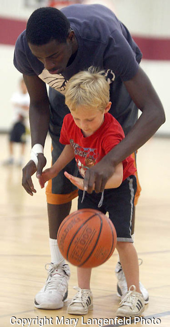 Keaton Cooper, 5, with a height of 3 feet, 10 inches, gets some help in learning how to dribble from Middleton's Antoine Buchanon, a 6-foot-four senior-to-be.