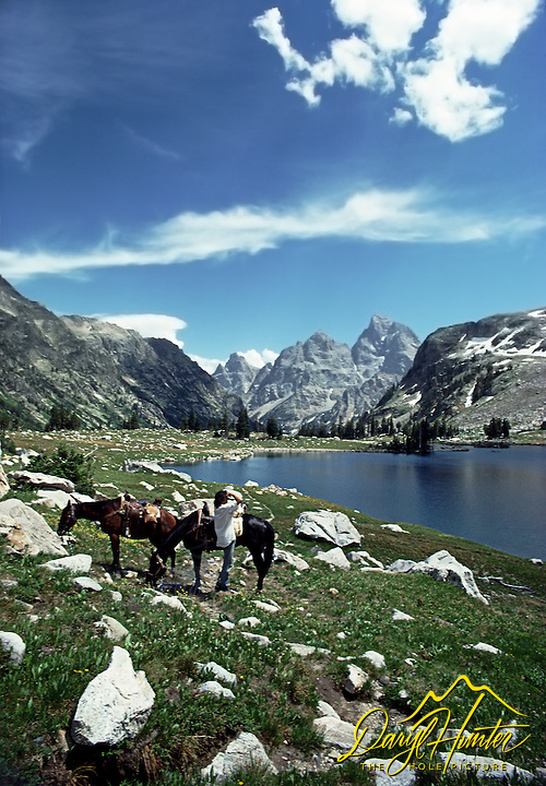 Horseback rider takes a moment to admire Lake Solitude in the Grand Teton Mountains