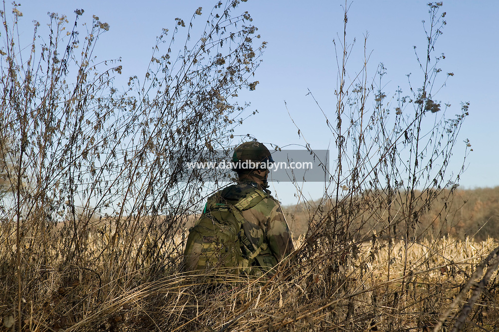 A member of the French Foreign Legion stands on look out after jumping over a plain north of Tarbes, France, during a full scale multi-force exercise, 12 December 2007.