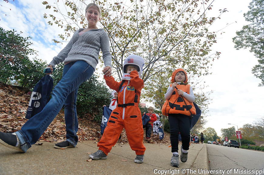 Astronaut Thaxton Van Every and Pumpkin Nora Quong make their way down the street as children from Willie Price daycare go trick or treating at the Chancellor's house.  Photo by UM Photographer Kevin Bain.