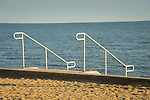 Metal railings to beach highlighted by sun.