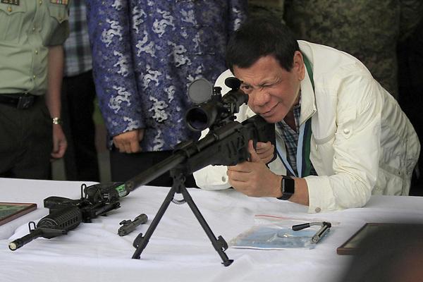 FRM101 MANILA (FILIPINAS), 28/06/2017.- El presidente filipino Rodrigo Duterte comprueba un rifle de francotirador CS/LR4A de fabricación china durante una ceremonia de entrega de armas en la base militar de Pampanga, Filipinas hoy 28 de junio de 2017. EFE/King Rodriguez **SÓLO USO EDITORIAL/NO VENTAS**