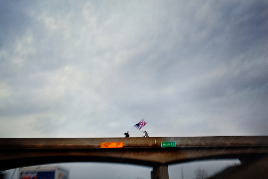 "Near Lowell Township, Michigan, April 10, 2010 - Tea Party supporters carried a flag to an overpass to show their support as Tea Party Express busses passed by en route to a rally in Lansing. The Tea Party Express tour titled ""Just Vote Them Out"" is taking an aggressive approach by targeting Democratic incumbents competitive districts, as well as Republicans deemed not conservative enough who are facing primary challenges from more conservative candidates. While not endorsing any candidates so far, the Tea Party Express does not hide its desire to replace incumbents with new conservatives that more closely hew to its goals of smaller government and less taxes.."