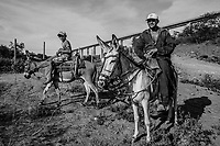 PAULISTANA, BRAZIL - FEBRARY 04, 2014: A young vaquiero, or cowboy, and his father pause as they herd cows(unseen) to pasture below the towering 150ft high pillars of an abandoned bridge destined to be part of the Transnordestina railway project on February04, 2014 near Paulistana, Piaui province, in Northern Eastern Brazil. The Transnordestina, a 1,400-mile railroad project which a steel company began building in 2006 in northeast Brazil, offers a view into the pitfalls plaguing projects big and small across Brazil. Intended to be finished in 2010 at a cost of about $1.8 billion, the railroad is now expected to cost at least $3.2 billion, with ample financing from state banks, and be completed sometime around 2016. Long stretches along the routes where freight trains were already supposed to be running now stand completely deserted. Wiry vaqueiros, or cowboys, herd cattle in the shadow of futuristic railroad bridges with massive concrete pillars towering 150 feet above parched valleys. <br /> <br /> Daniel Berehulak for The New York Times