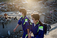 School children make their way home amongst the devastation of Minamisanriku, Myiagi, Japan. The fishing port of Minamisanriku, Miyagi, Japan was devastated by the tsunami where the popultion was reduced from 18,000 to about 8,000