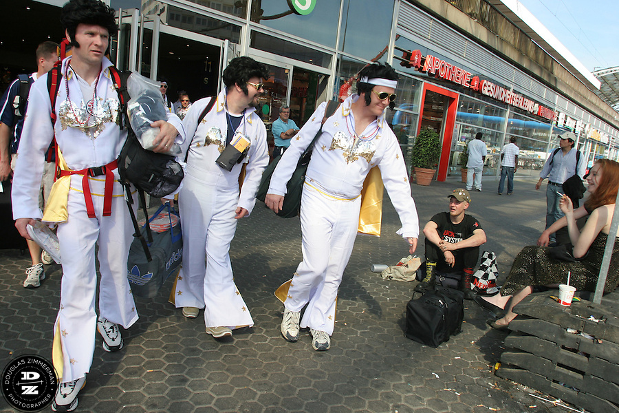 """USA National Soccer Team fans, (left to right) Pat Ryan of Kansas City, MO, Chris Widmer of Columbia, MO,  and Philippe Lechevin of Kansas City, MO, dressed up in flight suits as the American Icon Elvis, were greeted with smiles by onlookers while exiting from the  Cologne train station.  The group was traveling by train to Cologne, Germany from Düsseldorf Airport and their hotel. They arrived at Düsseldorf Airport in Germany on Saturday morning, June 10th, 2006 after an overnight flight from JFK airport in New York City.  The fans were part of a tour group, called """"2006 World Cup Trip"""" arraigned by Pat Ryan from Kansas City, MO by his travel company """"Ryan Adventures. They were among the thousands of American fans who have descended on Germany to support the USA National team during the 2006 FIFA World Cup. The first game for the USA is against the Czech Republic in Gelsenkirchen on Monday June 12th...For a website of the tourgroup:..http://www.2006worldcuptrip.com/..Pat Ryan can also be reached by cell phone with any questions 1.913.963.7168"""