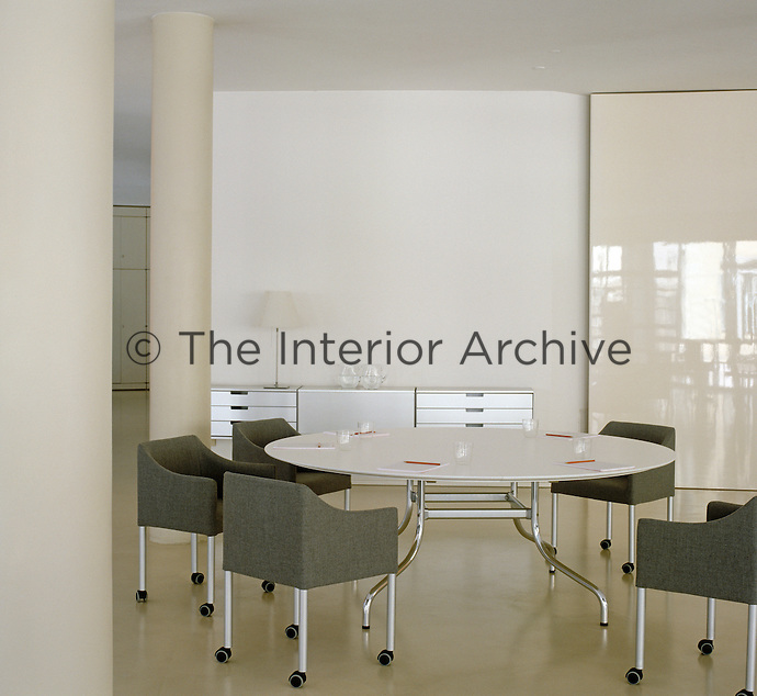 A round table and grey chairs, both by Vico Magistretti, furnish this all white work space