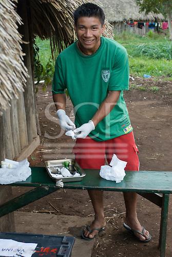 Xingu Indigenous Park, Mato Grosso State, Brazil. Nursing assistant Tawaiu Yudja preparing his dental equipment.