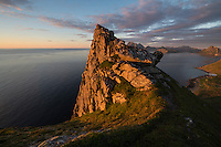 Steep summit ridge of Hornet rises from sea in evening light, Flakstadøy, Lofoten Islands, Norway