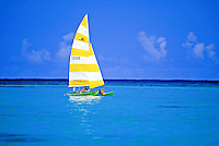 Catamaran with yellow & white sail in blue-green waters off Lanikai.