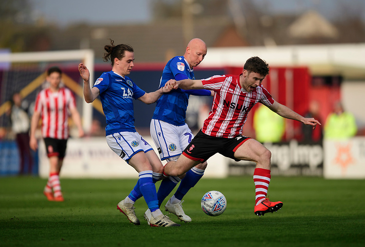Lincoln City's Shay McCartan is fouled by Macclesfield Town's Ben Stephens, left, and Macclesfield Town's Danny Whittaker<br /> <br /> Photographer Chris Vaughan/CameraSport<br /> <br /> The EFL Sky Bet League Two - Lincoln City v Macclesfield Town - Saturday 30th March 2019 - Sincil Bank - Lincoln<br /> <br /> World Copyright © 2019 CameraSport. All rights reserved. 43 Linden Ave. Countesthorpe. Leicester. England. LE8 5PG - Tel: +44 (0) 116 277 4147 - admin@camerasport.com - www.camerasport.com