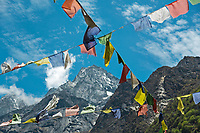 The sacred mountain of Mount Khumbi Yul Lha with prayer flags in the foreground, Khumbu, Nepal