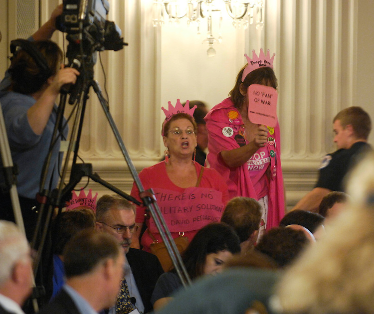 "WASHINGTON, DC - Sept. 10: Members of the anti-war group Code Pink shout during Gen. David H. Petraeus and U.S. Ambassador to Iraq Ryan Crocker testify during the joint House Armed Services and House Foreign Affairs hearing on Iraq. U.S. Capitol Police removed them from the room. The military can reduce the level of U.S. forces in Iraq to their pre-surge level by next summer without jeopardizing recent security gains, Gen. David H. Petraeus told lawmakers Monday. ""I have recommended a drawdown of the surge forces in Iraq,"" due to a slowly improving security situation and the increasing capability of Iraqi forces to accept responsibility for security, Petraeus told a joint hearing of the House Armed Services and Foreign Affairs committees. The surge of troops ordered by President Bush in January is having its desired effect, Petraeus declared. ""The military objectives of the surge are by and large being met,"" Petraeus testified. He said he had recommended the gradual withdrawal of five Army brigade combat teams, two Marine battalions, and a Marine Expeditionary Unit. The MEU would leave Iraq later this month, and the first combat brigade would depart in mid-December. The reductions would drop the number of U.S. troops in Iraq from approximately 160,000 to the pre-surge level of around 130,000 by July 2008. After next summer, ""force reductions will continue beyond the pre-surge levels,"" Petraeus said, although he said he would not be ready to discuss specifics until mid-March 2008. Petraeus' recommendations resemble a plan suggested by former Senate Armed Services Chairman John W. Warner, R-Va., last month, when he suggested bringing home about 5,000 troops by Christmas to show the Iraqi government that the U.S. military commitment is not indefinite. Appearing with Petraeus was U.S. Ambassador to Iraq Ryan Crocker, who said he does not expect rapid progress over the next six months on the 18 benchmarks for Iraqi government progress laid out in the fiscal 2007 emergenc"