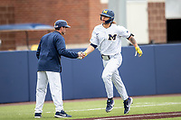 Michigan Wolverines outfielder Jordan Brewer (22) is greeted by third base coach Nick Schnabel (23) after hitting a home run against the Rutgers Scarlet Knights on April 27, 2019 in the NCAA baseball game at Ray Fisher Stadium in Ann Arbor, Michigan. Michigan defeated Rutgers 10-1. (Andrew Woolley/Four Seam Images)