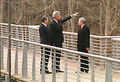Shepherdstown, West Virginia - January 3, 2000 -- United States President Bill Clinton, center, points to the Potomac River as he walks across a 200 foot-long pedestrian bridge with Prime Minister Ehud Barak of Israel left, and Syrian Foreign Minister Farouk al_Shara of Syria, right, at the start of the Israeli-Syrian Peace Talks on 3 January, 2000..Credit: Ron Sachs / CNP