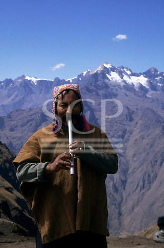 Inca Trail, Peru. Local Quechua indian guide in brightly coloured hat and brown poncho playing homemade flute.