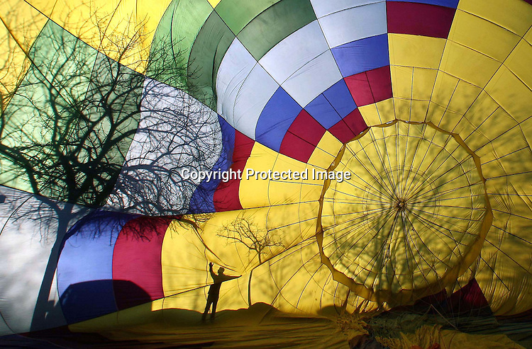 A person is reflected in a hot air balloon as it is inflated before flight in the town of Yountville, California.