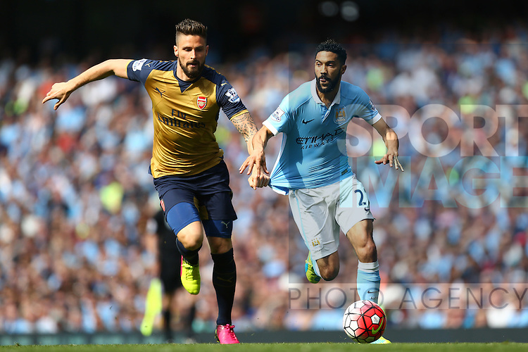 Arsenal's Olivier Giroud tugs at the shirt of Gael Clichy of Manchester City during the Barclays Premier League match at the Etihad Stadium. Photo credit should read: Philip Oldham/Sportimage