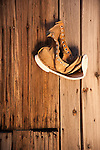 A dried and distorted leather boot hanging on the wall on the wall inside an abandoned building at the Baldwin Mine, Jackson Range, Nev.