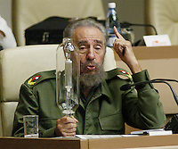Cuban President Fidel Castro holds a ligth bulb while talking during a second session at the Cuban Parliament, in the Palace of Conventions, Friday, Dec. 23, 2005 in Havana, Cuba. The Cuban Gobernt announced it had turned a corner in its recovery from severe financial crisis, reporting 11.8 percent growth in 2005 using its own method for calculating gross domestic product.  Credit: Jorge Rey/MediaPunch