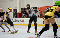 Front pack referee Al Capwn3d signals a forearm penalty while yelling and keeping an eye on the blockers.  Jam referee Override skates inside of Al, while the penalty wrangler rushes to get out of the way.  Portions of this image not central to the content have been digitally altered.