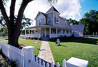 A suburban house and yard with a white picket fence, swing and child at play.