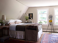 The master bedroom is comfortably if simply furnished and the unframed portrait on the wall is by the owner Frank Muytjens
