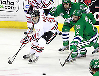 Nebraska Omaha's James Polk and Mercyhurst's Nick Jones eye a loose puck. (Photo by Michelle Bishop)