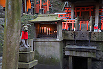 Kyoto City, Japan<br /> Small torii gates and offertory candles on an alter of the Fushimi Inari Shrine (Shinto)
