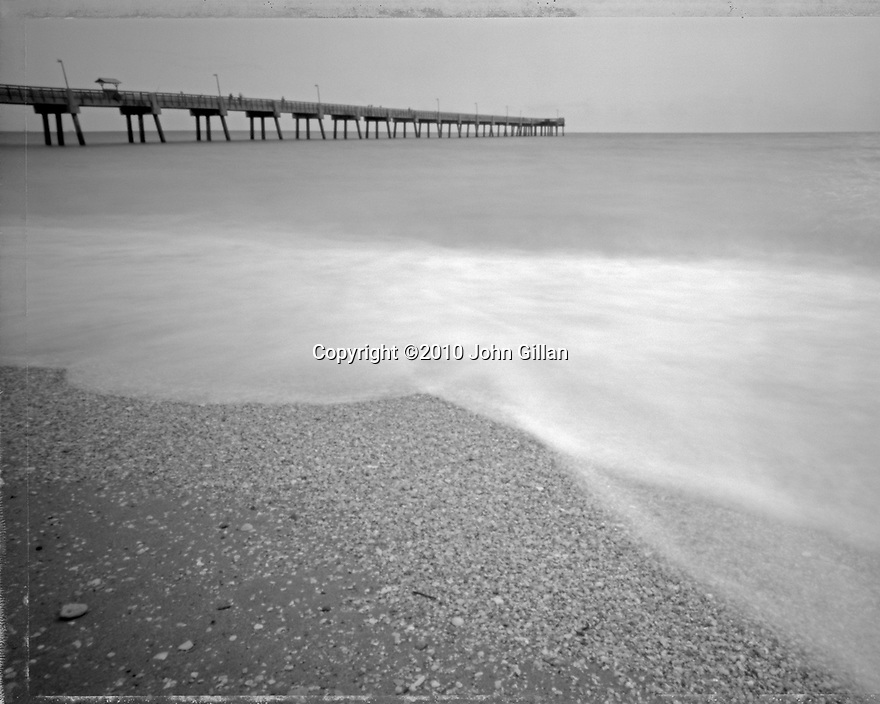Black and white pinhole photograph of the calm water's edge of the Atlantic ocean and Dania Pier.