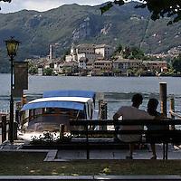Coppia osserva l'Isola San Giulio dal porto di Orta..A couple look San Giulio Island from harbour of Orta