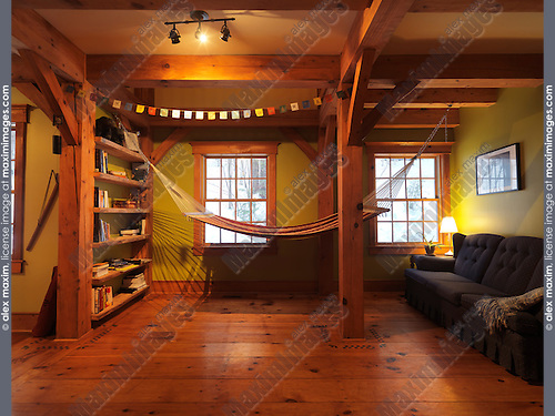 Lounge room with a hammock in a Canadian timber frame country house, interior with a lot of wood, Muskoka, Ontario, Canada