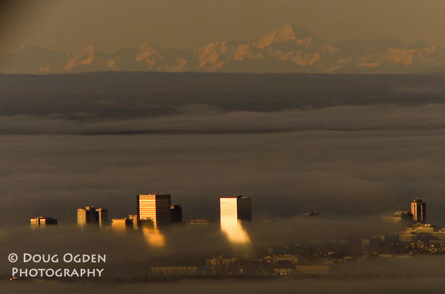 Setting sun reflecting off the buidlings into the fog with Mt. McKinley in the background, Anchorage, Alaska