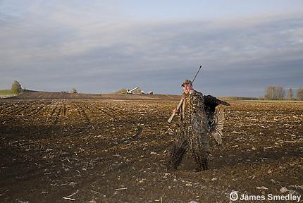 Hunter carrying wild turkey