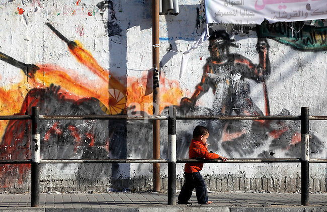 A Palestinian boy stands next to the graffiti on the mural in a street displays a Palestinian resistant fires rockets,  in Gaza on November 13, 2012. Photo by Majdi Fathi