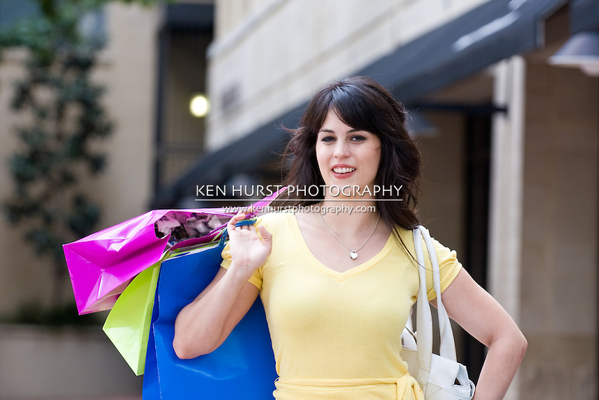 Beautiful young brunette woman on a shopping trip in the city carrying colorful shopping bags.