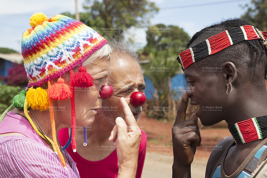 "Ethiopia. Southern Nations, Nationalities, and Peoples' Region. Omo Valley. Keyafer. Soizic Triennot (L) and Jean Marc Chetrit (R) wear both a glossy red plastic clown nose and talk to a man from the Bena tribe. Marc Vella is a french musician and a nomadic pianist. Over the last 25 years he has travelled with his Grand Piano in around forty countries to celebrate humanity. Creator of ""La Caravane amoureuse"" (The Caravan of Love) he takes people with him to say ""I love you"" to others and ""lovingly conquered"" their hearts and souls. Banna, Bana, and Benna are other spellings for the Bena people which are mainly agricultural people. The Omo Valley, situated in Africa's Great Rift Valley, is home to an estimated 200,000 indigenous peoples who have lived there for millennia. Southern Nations, Nationalities, and Peoples' Region (often abbreviated as SNNPR) is one of the nine ethnic divisions of Ethiopia 12.11.15 © 2015 Didier Ruef"