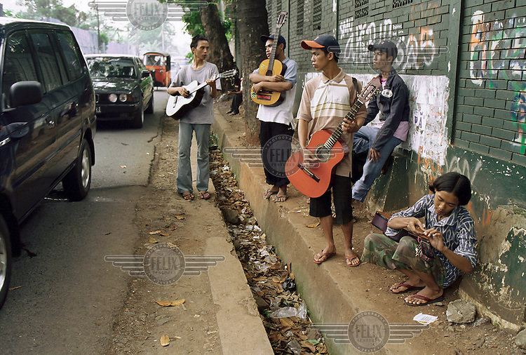 Young men try to earn money by busking, playing their guitars to car drivers waiting in a traffic jam...